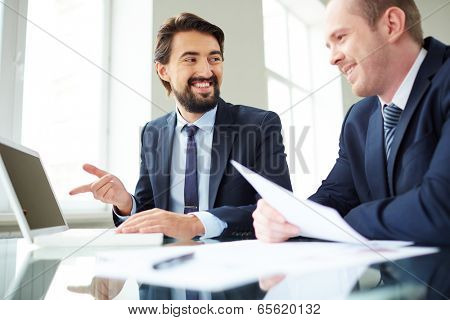 Image of young businessman pointing at laptop screen while explaining ideas to his colleague at meeting