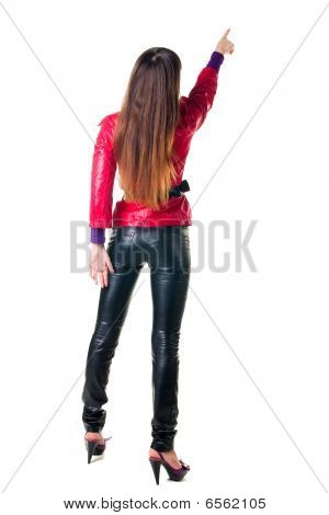 Young Woman Points At Wall. The Rear View