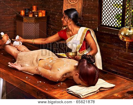 Woman having Ayurveda massage with pouch of rice.