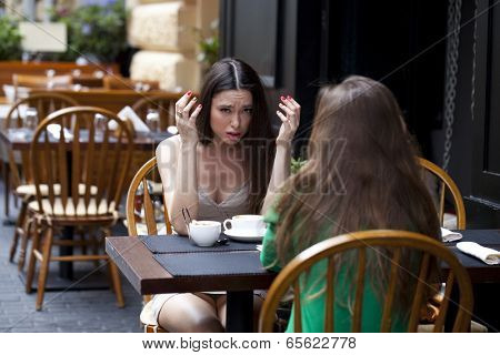 Two best friends solve their problems sitting in cafe