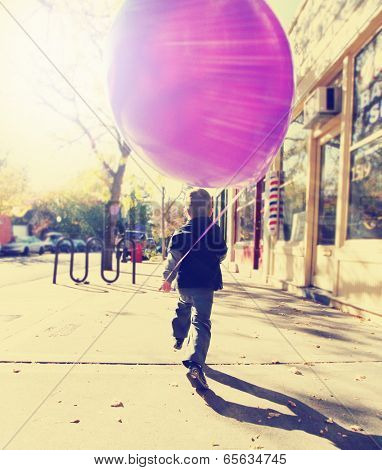 little boy running with a balloon done with a retro vintage instagram filter