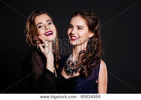 Two happy women in  black cocktail dresses