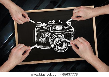 Composite image of multiple hands drawing camera with chalk against blackboard