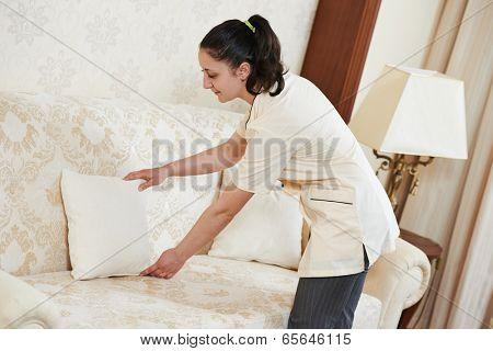 Hotel service. female housekeeping worker maid making order at inn room
