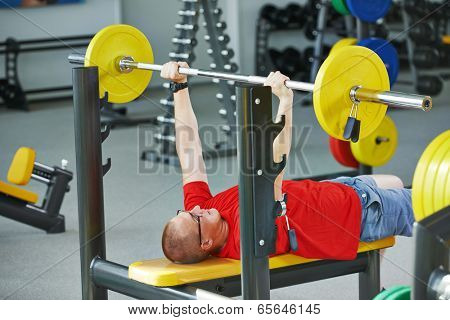 athlete man at arm muscles exercises with training weight in fitness club gym