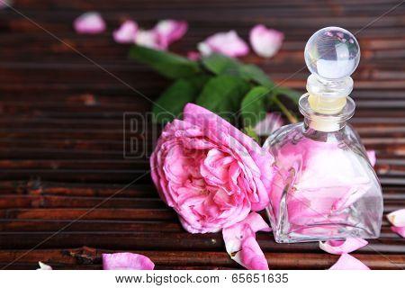 Rose oil in bottle on bamboo mat background