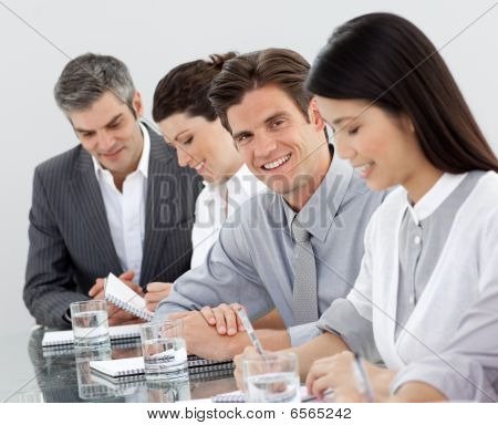 Multi-ethnic Business People Taking Notes At A Presentation