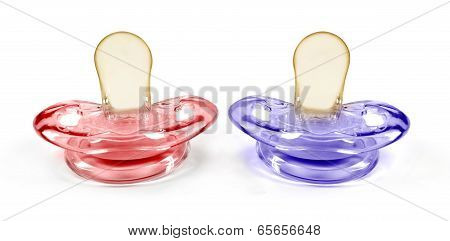 two baby pacifiers on an isolated white background