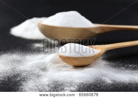 Spoons of baking soda on black background