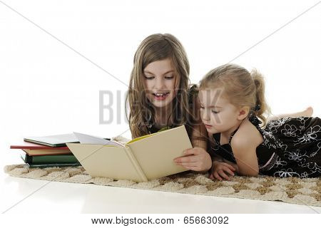 An older elementary girl reading a story to her interested little sister.  On a white background, with space on the left for your text.