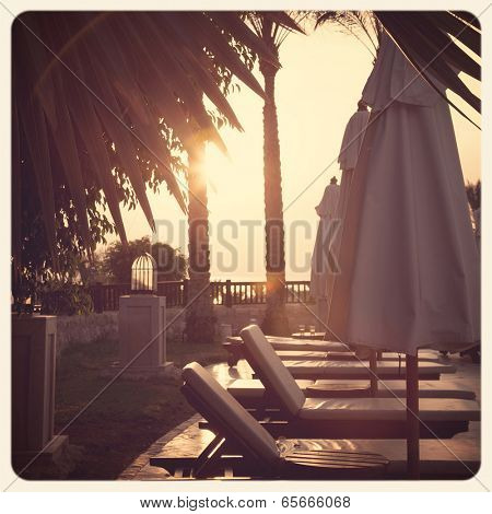 Sun-loungers and parasols at dawn. Sharm el Sheik, Egypt. Filtered to look like an aged instant photo.