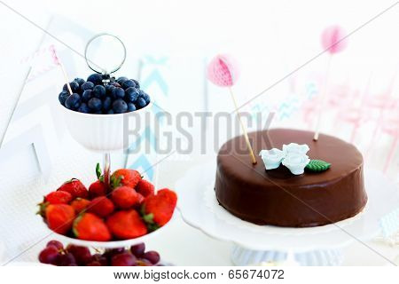 Blueberries, strawberries, grapes and a chocolate cake on a dessert table at party