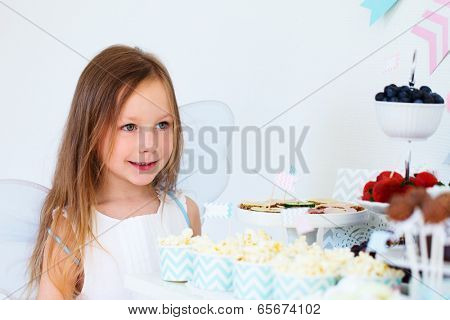 Adorable little fairy girl on a birthday party in front of dessert table