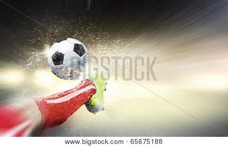 Close up image of footballer foot kicking the ball