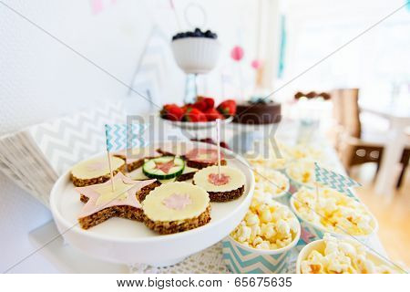 Berries, popcorn, canapes, candies and a chocolate cake on a dessert table at party