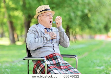 Senior man choking in park and holding an inhaler