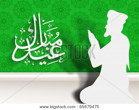 Beautiful paper design of a religious muslim man praying and arabic islamic calligraphy of text Eid Mubarak on green and grey background.