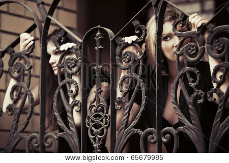 Two sad young women at the cast iron fence