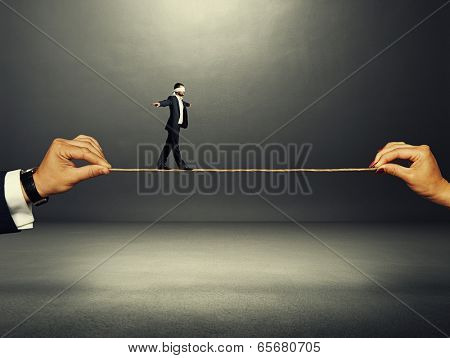 man with the blindfold walking on the rope over dark background