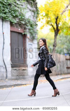 Urban young woman walking in leather jacket in city crossing streets in full length in autumn fall. Trendy modern female living city lifestyle. Multiracial Asian Caucasian model.