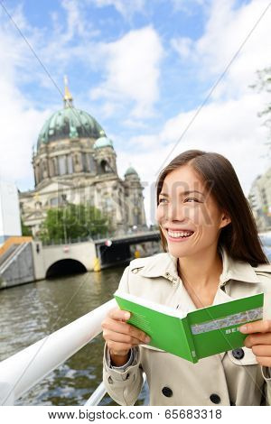Tourist woman on boat tour Berlin, Germany having fun smiling happy while enjoying mini cruise reading guidebook. Europe travel vacation holiday concept. Multiracial Asian Caucasian woman.