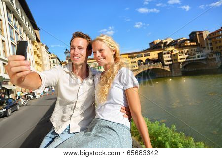 Happy couple selfie photo on travel in Florence. Romantic woman and man in love smiling happy taking self portrait outdoor by Ponte Vecchio during vacation holidays in Florence, Tuscany, Italy, Europe