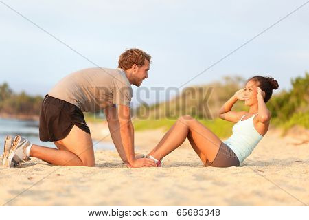 Fitness woman training situp crunches with personal trainer instructor. Young couple happy working out in sand on beach. Beautiful Asian female model and male fitness model holding her feet exercising