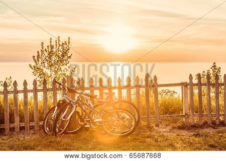 Bicycles leaning on a fence by the beach