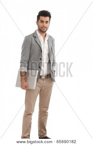 Handsome casual young man smiling, holding laptop.