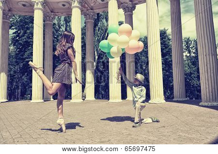 Elegant beautiful teen girl dancer in pointes posing outdoor with little boy holding colored ballons. Vintage toned.