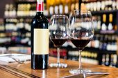 image of bottles  - Bottle of red wine and two glasses in wine shop - JPG
