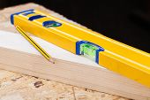 pic of joinery  - Close up view of a colorful yellow carpenters level ruler and right angle lying on planks of new hardwood together with a pencil for measurements in a carpentry construction DIY and joinery concept - JPG