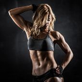 stock photo of muscle builder  - Smiling athletic woman showing muscles on dark background - JPG