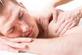 picture of deep-tissue  - Handsome man lying in a spa salon enjoying a deep tissue back massage - JPG