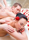 image of deep-tissue  - Attractive couple lying  in a spa salon enjoying a deep tissue back massage together - JPG