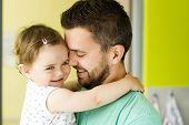 picture of daughter  - Indoor portrait of young father hugging his little daughter - JPG
