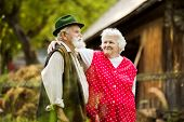 stock photo of farmhouse  - Outdoor portrait of old farmers couple standing by their farmhouse - JPG