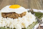 stock photo of loco  - Loco Moco a traditional Hawaiian dish of teriyaka flavored ground beef patty and a fried egg on a bed of rice smothered in gravy
