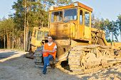 foto of heavy equipment operator  - positive driver of heavy equipment rests in the workplace - JPG