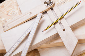foto of joinery  - Close up view of a colorful yellow carpenters level ruler and right angle lying on planks of new hardwood together with a pencil for measurements in a carpentry construction DIY and joinery concept - JPG