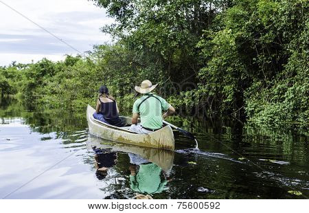 Couple riding canoe in Pantanal River, Brazil