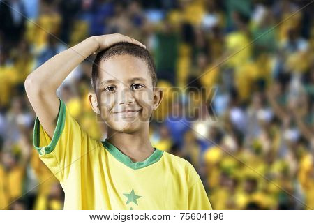 Brazilian little boy putting his hand on his head in the stadium