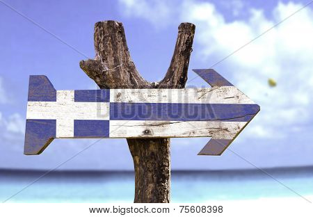 Greece wooden sign with a beach on background