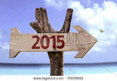 2015 wooden sign with a beach on background