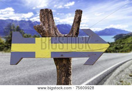 Sweden wooden sign with a landscape on background
