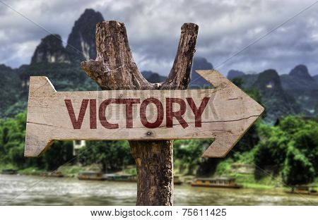 Victory wooden sign with a rural background