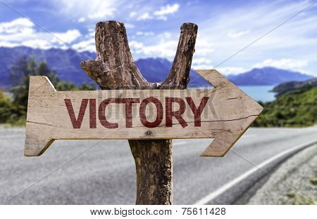 Victory wooden sign with a street background