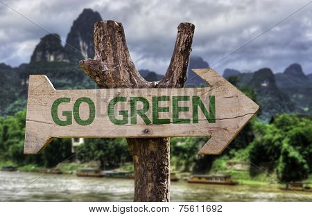 Go Green wooden sign with a forest background