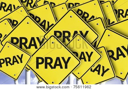 Pray written on multiple road sign