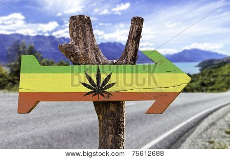 Rasta Flag With Marijuana Leaf wooden sign with a street background